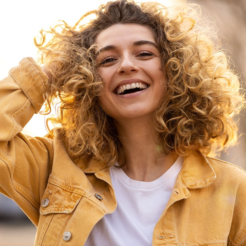 smiling woman with curly brown-blonde hair wearing yellow jean jacket