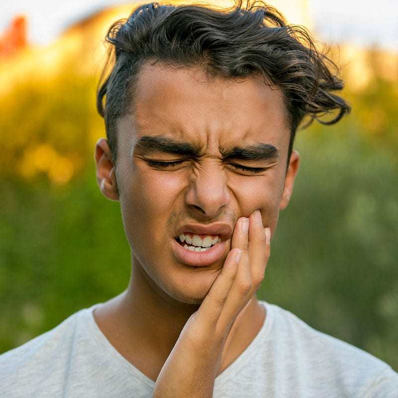 teen boy holding the side of his mouth in pain