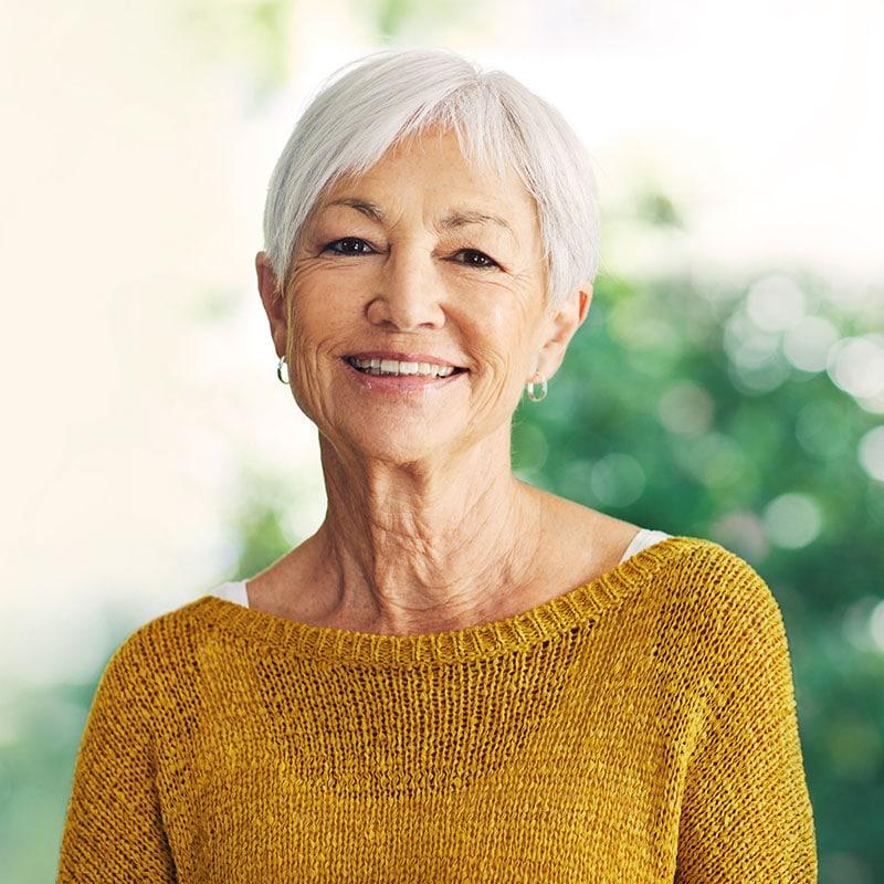 senior woman wearing yellow sweater, smiling