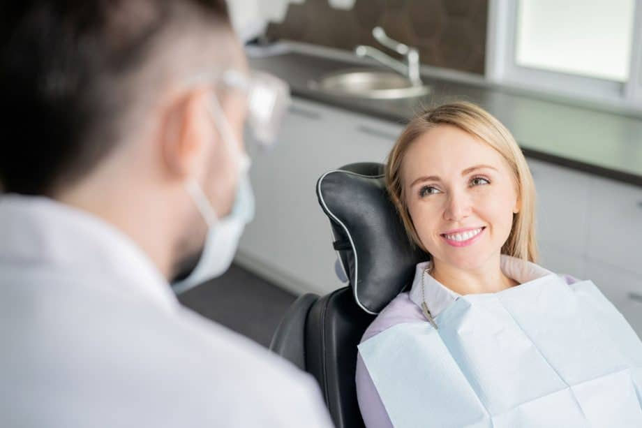 smiling female patient in dental chair