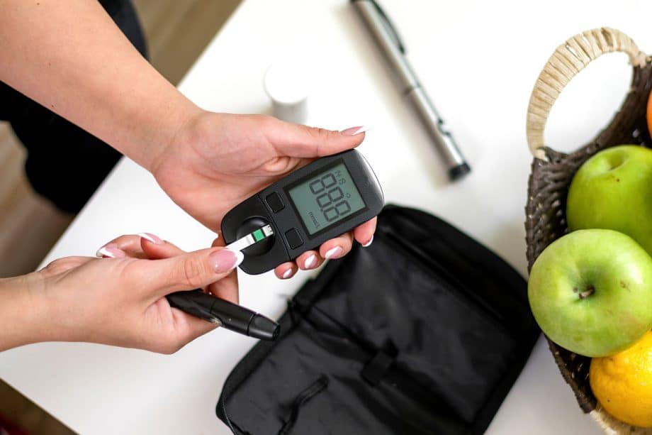 woman testing blood sugar level on electronic tester