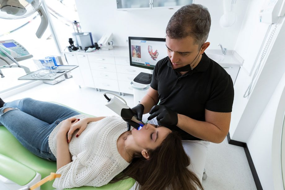 dentist using technology to examine patient's mouth