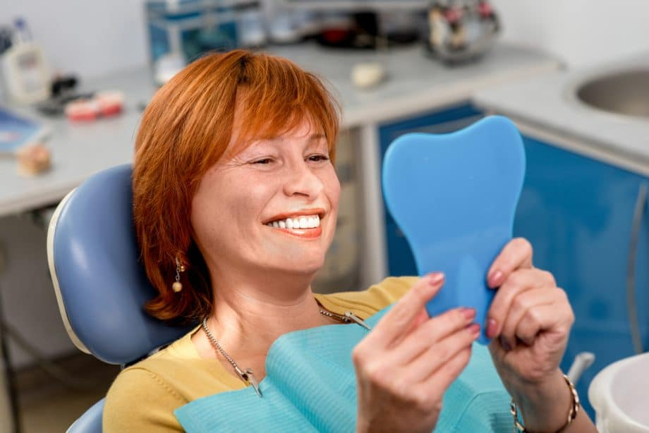 red-headed woman in exam chair holding mirror and smiling