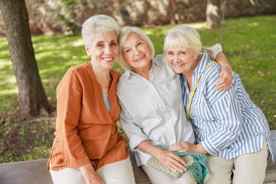 three senior woman in park, sitting on cement bench