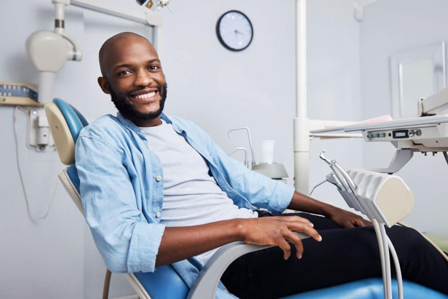 man in dental chair, smiling