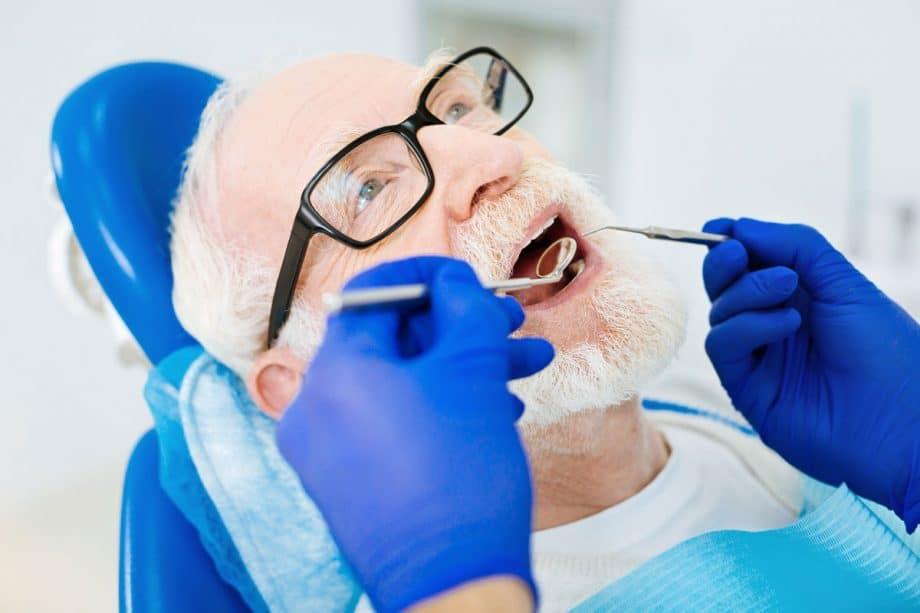 older man in dental chair getting dental exam