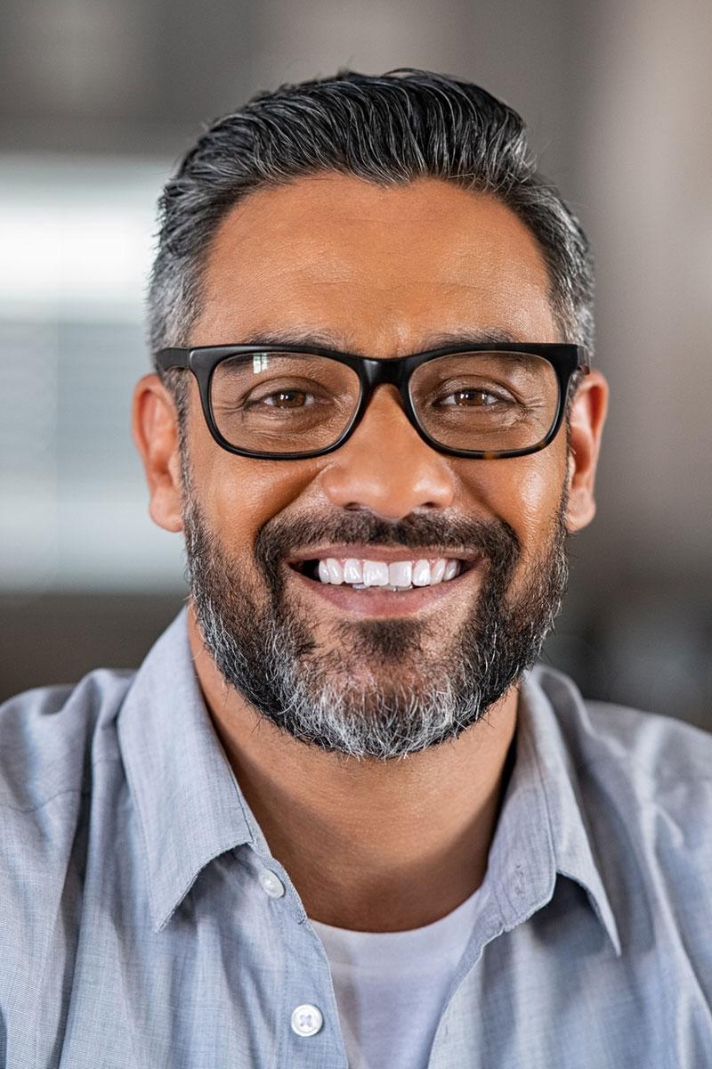 smiling man with black framed glasses